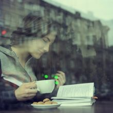 You are not alone - Smiling woman reading in a coffee shop