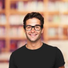 What kind of indie-publisher are you? - Smiling bespectacled man in front of a bookcase